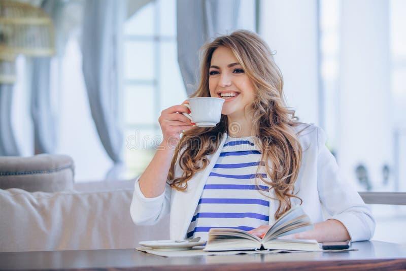 Όμορφο νέο κορίτσι στον υπαίθριο καφέ που διαβάζει το α στοκ φωτογραφία με δικαίωμα ελεύθερης χρήσης