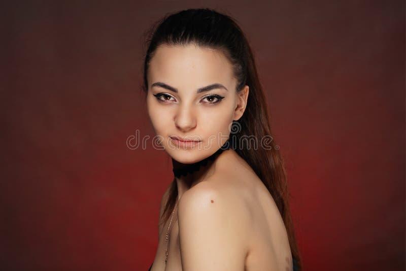 Όμορφο νέο κορίτσι στο στούντιο στο κόκκινο υπόβαθρο στοκ εικόνα με δικαίωμα ελεύθερης χρήσης