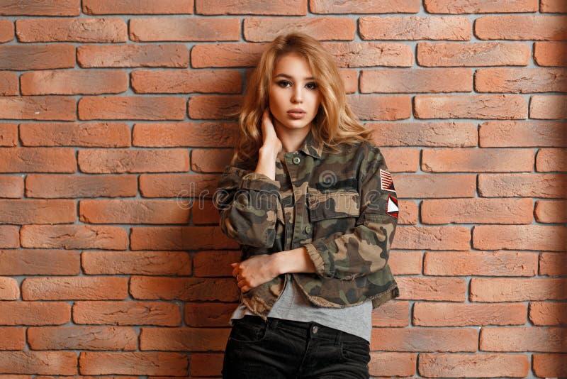 Όμορφο νέο κορίτσι στο στρατιωτικό σακάκι κοντά στον τούβλινο τοίχο στοκ φωτογραφίες με δικαίωμα ελεύθερης χρήσης