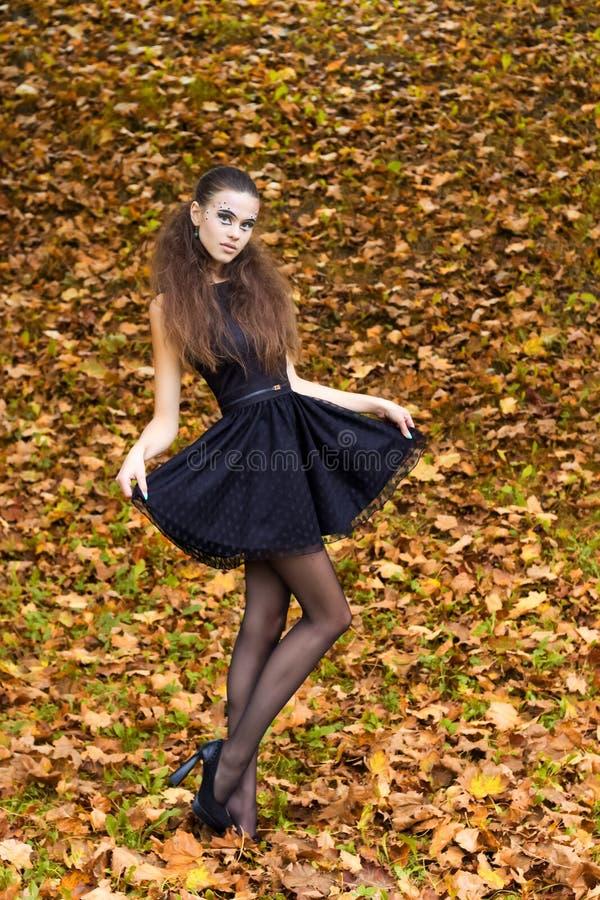 Όμορφο νέο κορίτσι στο υπόβαθρο των φύλλων στην ημέρα φθινοπώρου στην οδό με τη φαντασία makeup σε ένα μαύρο φόρεμα στοκ εικόνες