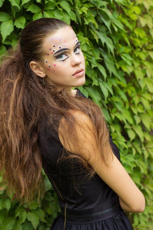 Όμορφο νέο κορίτσι στο υπόβαθρο των φύλλων στην ημέρα φθινοπώρου στην οδό με τη φαντασία makeup σε ένα μαύρο φόρεμα στοκ φωτογραφία με δικαίωμα ελεύθερης χρήσης