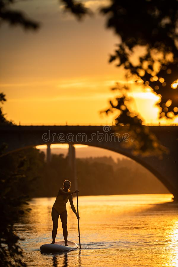 Όμορφο, νέο κουπί γυναικών που επιβιβάζεται σε μια καλή λίμνη στο θερμό αργά το απόγευμα φως στοκ φωτογραφίες