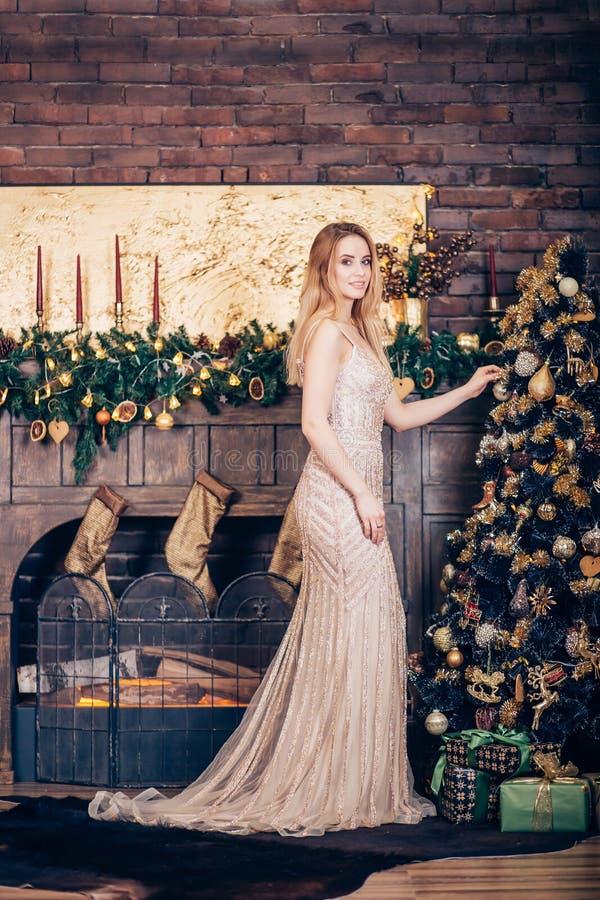 Όμορφο νέο ξανθό κορίτσι σε ένα μακρύ χρυσό φόρεμα που χαμογελά και που διακοσμεί το χριστουγεννιάτικο δέντρο κοντά στην εστία στοκ φωτογραφίες με δικαίωμα ελεύθερης χρήσης