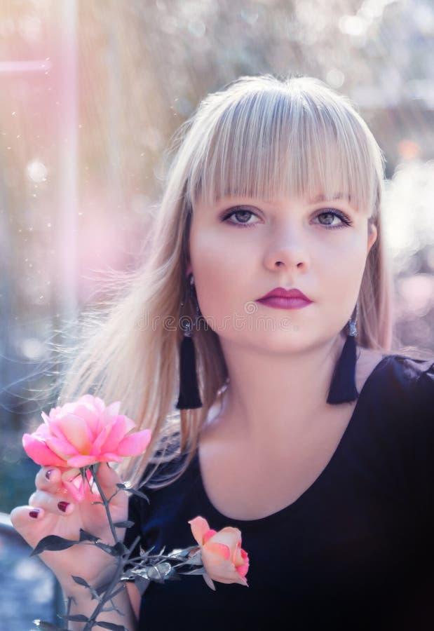 Όμορφο νέο ξανθό κορίτσι στη φυτεία με τριανταφυλλιές στοκ φωτογραφία με δικαίωμα ελεύθερης χρήσης