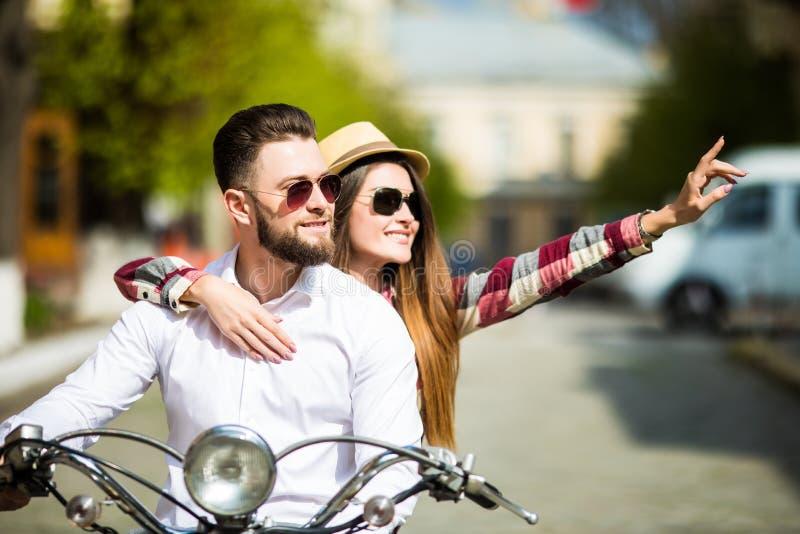 Όμορφο νέο οδηγώντας μηχανικό δίκυκλο ζευγών μαζί ενώ ευτυχής γυναίκα που δείχνει μακριά και που χαμογελά στοκ εικόνες με δικαίωμα ελεύθερης χρήσης