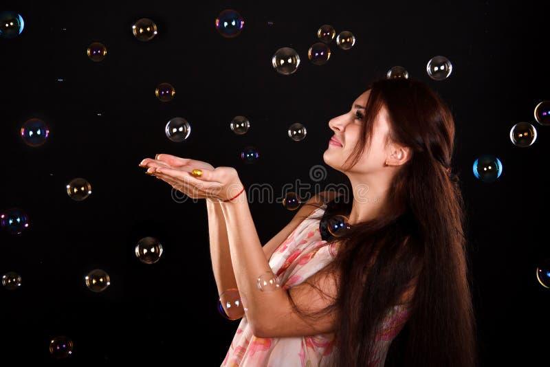 Όμορφο νέο παιχνίδι γυναικών με τις φυσαλίδες σαπουνιών στοκ φωτογραφία με δικαίωμα ελεύθερης χρήσης