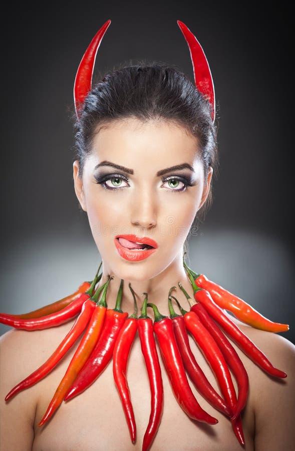 Όμορφο νέο πορτρέτο γυναικών με το κόκκινο - καυτά και πικάντικα πιπέρια στοκ φωτογραφία