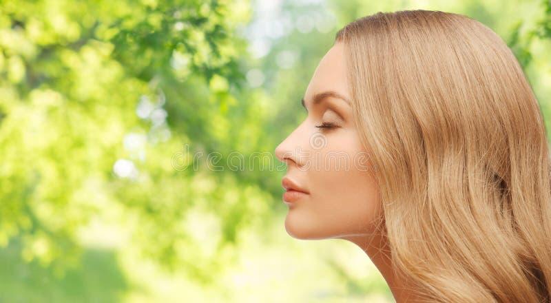Όμορφο νέο πρόσωπο γυναικών πέρα από το φυσικό υπόβαθρο στοκ εικόνες