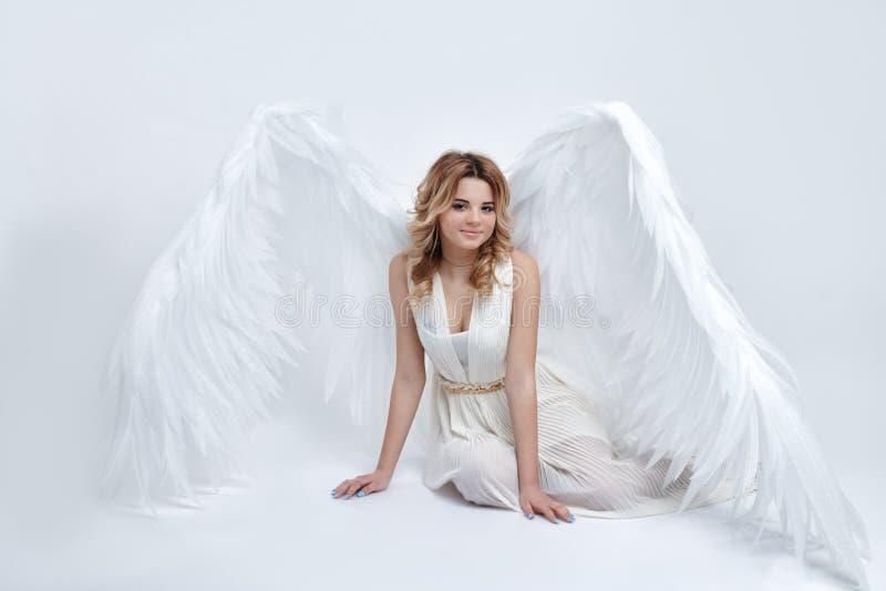 Όμορφο νέο πρότυπο με τα μεγάλα φτερά αγγέλου που κάθονται στο στούντιο στοκ εικόνες