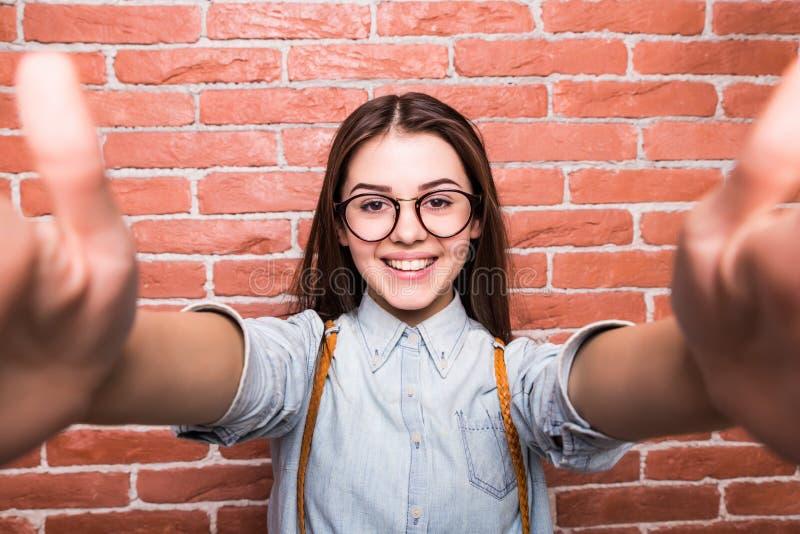 Όμορφο νέο σκοτεινός-μαλλιαρό κορίτσι στα περιστασιακά ενδύματα και eyeglasses που θέτουν, που χαμογελούν και που κάνουν selfie στοκ φωτογραφίες