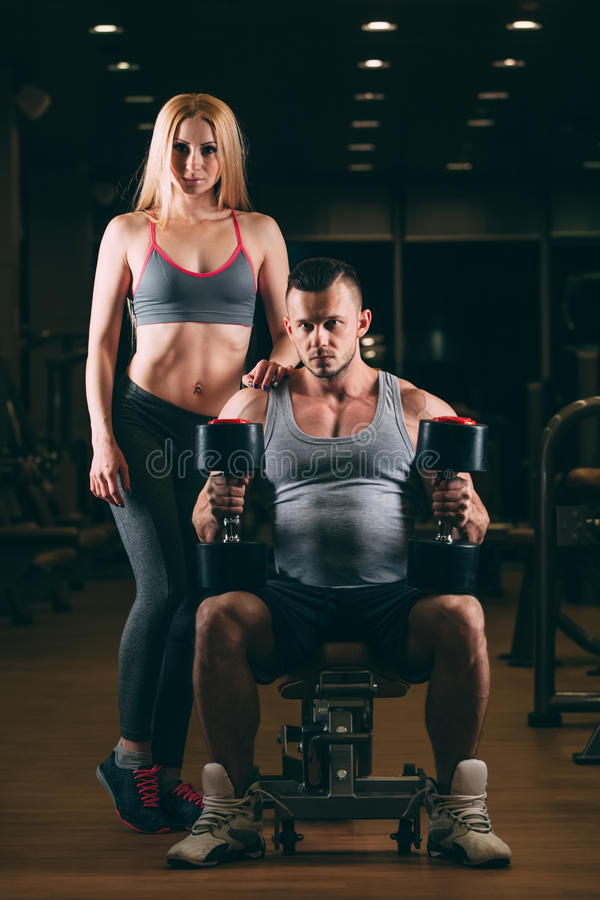 Όμορφο νέο φίλαθλο προκλητικό ζεύγος που παρουσιάζει μυ και workout στον αλτήρα γυμναστικής στοκ εικόνα