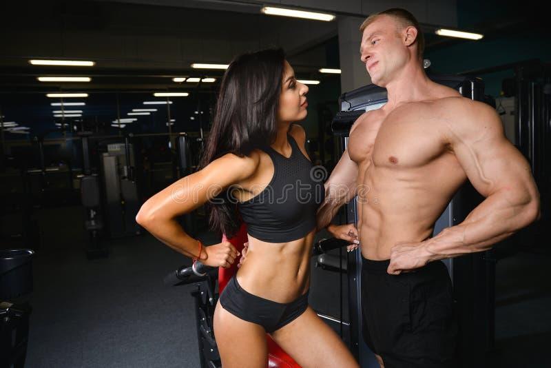 Όμορφο νέο φίλαθλο προκλητικό ζεύγος που παρουσιάζουν μυ και workout GY στοκ φωτογραφίες