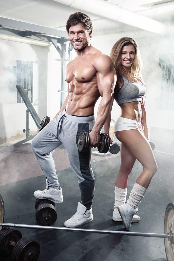 Όμορφο νέο φίλαθλο προκλητικό ζεύγος workout στη γυμναστική στοκ εικόνα με δικαίωμα ελεύθερης χρήσης