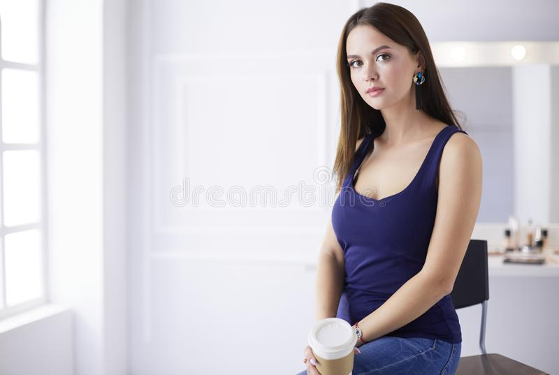 Όμορφο νέο φλυτζάνι καφέ εκμετάλλευσης γυναικών και κοίταγμα μακριά με το χαμόγελο καθμένος στην καρέκλα στοκ εικόνες με δικαίωμα ελεύθερης χρήσης