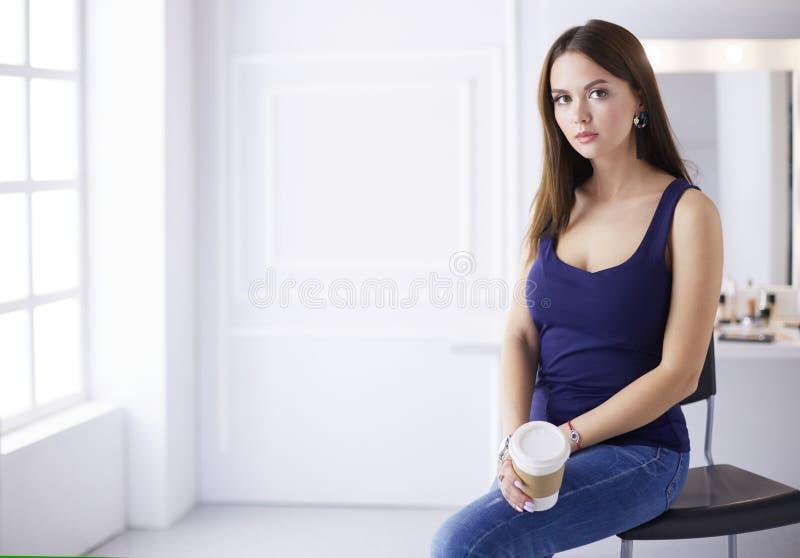 Όμορφο νέο φλυτζάνι καφέ εκμετάλλευσης γυναικών και κοίταγμα μακριά με το χαμόγελο καθμένος στην καρέκλα στοκ εικόνες