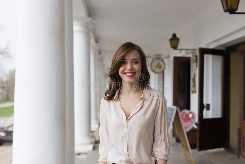 Όμορφο νέο χαμογελώντας κορίτσι με το σαγηνευτικό κόκκινο κραγιόν που στέκεται στη βεράντα του καφέ στήλες και φανάρια στο υπόβαθ στοκ φωτογραφία με δικαίωμα ελεύθερης χρήσης