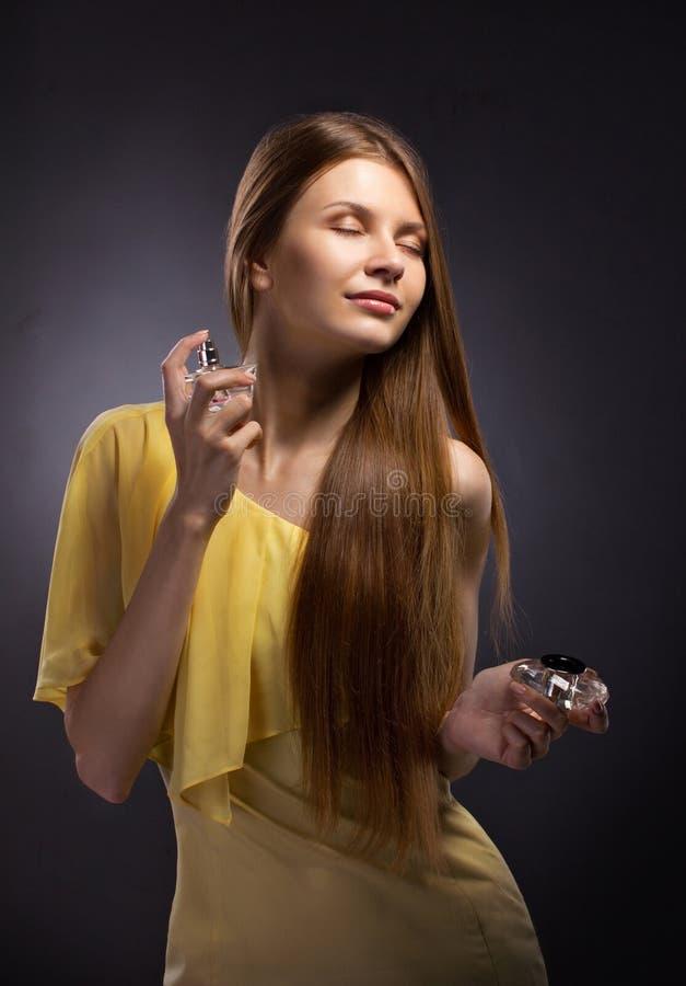 Όμορφο νέο ψεκάζοντας άρωμα γυναικών στοκ φωτογραφία
