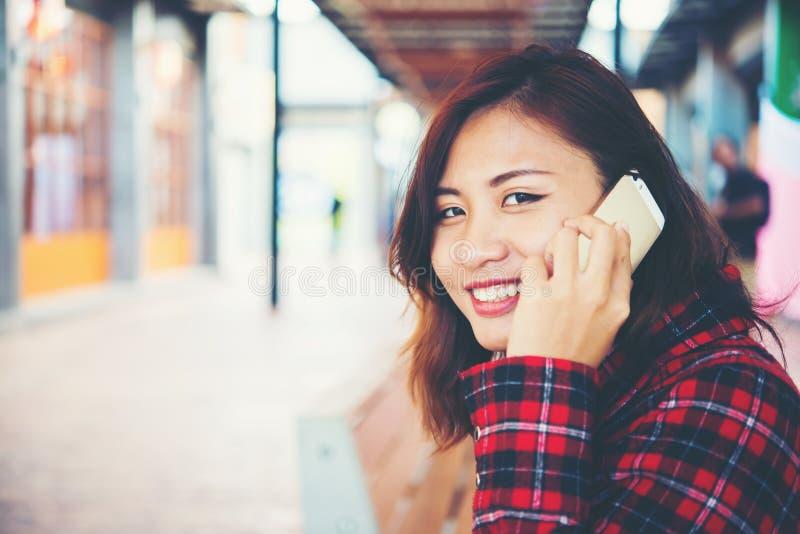 Όμορφο νέο hipster που μιλά στη συνεδρίαση smartphone σε έναν πάγκο στοκ εικόνα με δικαίωμα ελεύθερης χρήσης