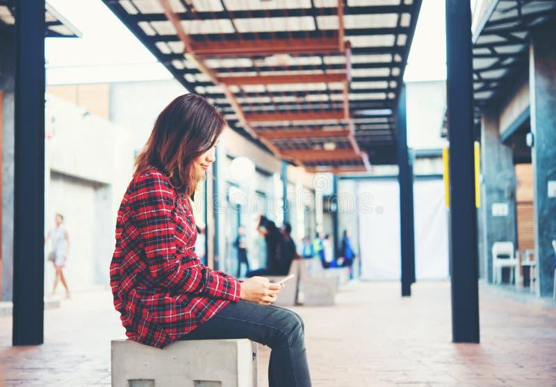 Όμορφο νέο hipster στη συνεδρίαση smartphone σε ένα β στοκ φωτογραφία
