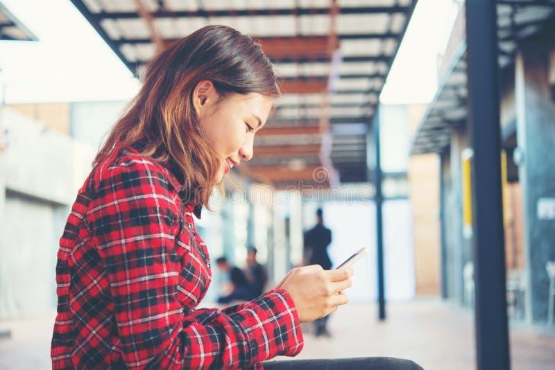 Όμορφο νέο hipster στη συνεδρίαση smartphone σε ένα β στοκ φωτογραφία με δικαίωμα ελεύθερης χρήσης