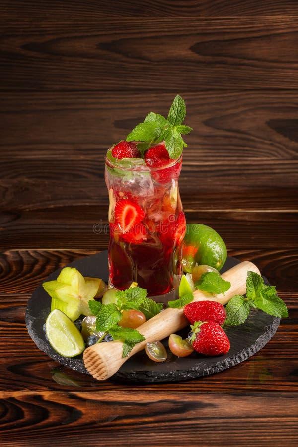 Όμορφο νόστιμο κοκτέιλ φραουλών με τη μέντα, τον πάγο, τον ασβέστη, και τα κομμάτια της φράουλας Θερινά αναζωογονώντας ποτά διάστ στοκ εικόνα