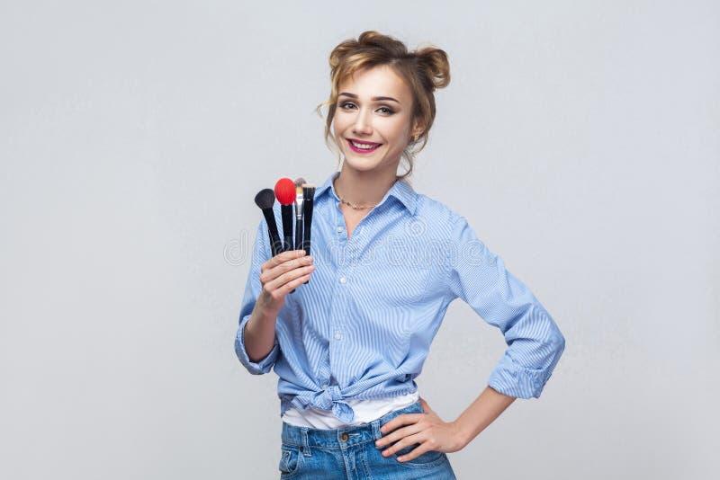 Όμορφο ξανθό κορίτσι ευτυχίας, που κρατά τη βούρτσα pofessional και το λ στοκ εικόνα με δικαίωμα ελεύθερης χρήσης