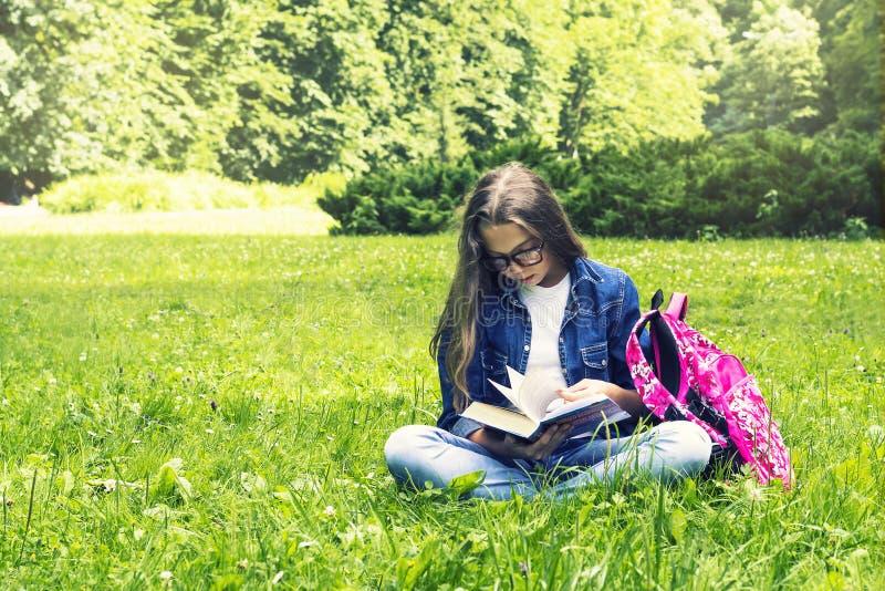 Όμορφο ξανθό κορίτσι μαθητριών στο πουκάμισο τζιν που διαβάζει ένα βιβλίο στη χλόη με ένα σακίδιο πλάτης στο πάρκο στοκ εικόνα με δικαίωμα ελεύθερης χρήσης