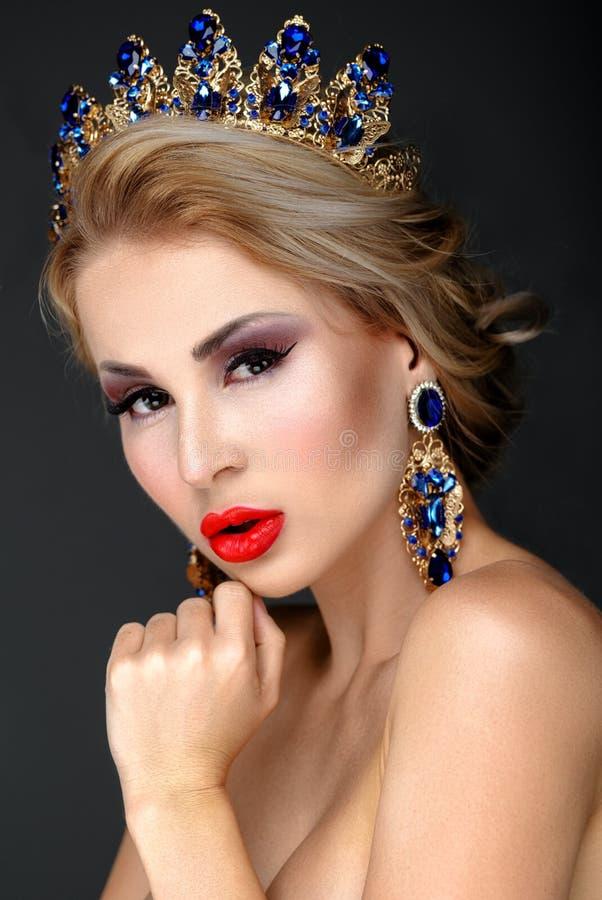 Όμορφο ξανθό κορίτσι με μια χρυσή κορώνα, τα σκουλαρίκια και το professi στοκ εικόνα