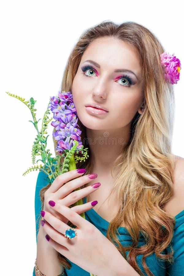 Όμορφο ξανθό κορίτσι με το φωτεινό makeup, τη μακροχρόνια κατσαρωμένη τρίχα και το ογκώδες κόσμημα που κρατούν έναν ανθίζοντας κλ στοκ φωτογραφία με δικαίωμα ελεύθερης χρήσης