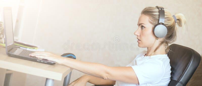Όμορφο ξανθό κορίτσι που ακούει τη μουσική στα ακουστικά στο σπίτι στοκ εικόνα