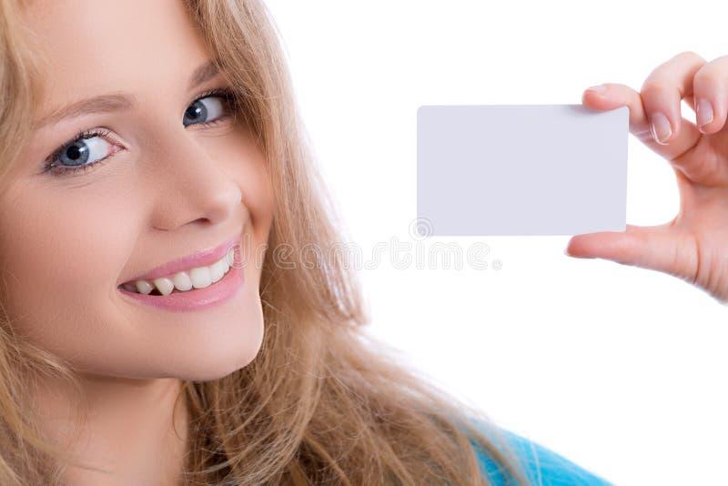 Όμορφο ξανθό κορίτσι που παρουσιάζει επαγγελματική κάρτα στοκ φωτογραφίες