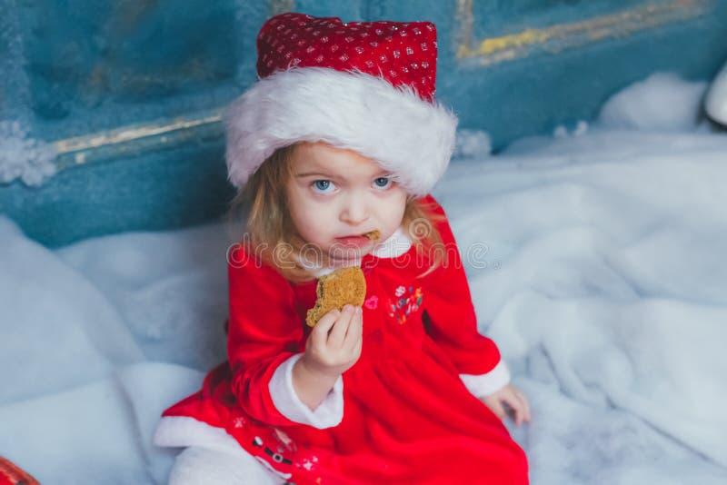 Όμορφο ξανθό κορίτσι που τρώει το μπισκότο στο κοστούμι Άγιου Βασίλη στοκ φωτογραφία