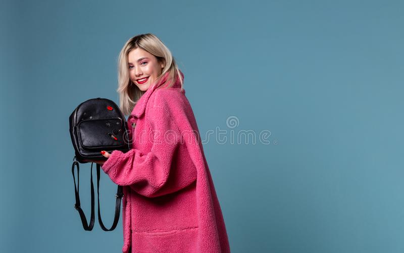 Όμορφο ξανθό κορίτσι που φορά το ρόδινο παλτό που κρατά το μαύρο σακίδιο πλάτης στα χέρια στοκ φωτογραφία