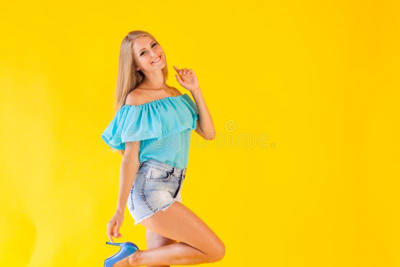 Όμορφο ξανθό κορίτσι σε ένα κίτρινο υπόβαθρο στο μπλε φόρεμα στοκ εικόνα