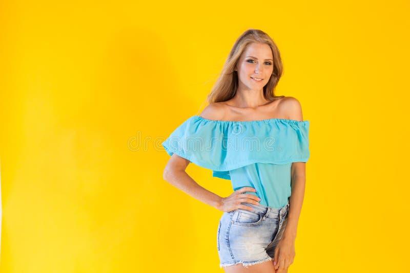 Όμορφο ξανθό κορίτσι σε ένα κίτρινο υπόβαθρο στο μπλε φόρεμα στοκ εικόνα με δικαίωμα ελεύθερης χρήσης