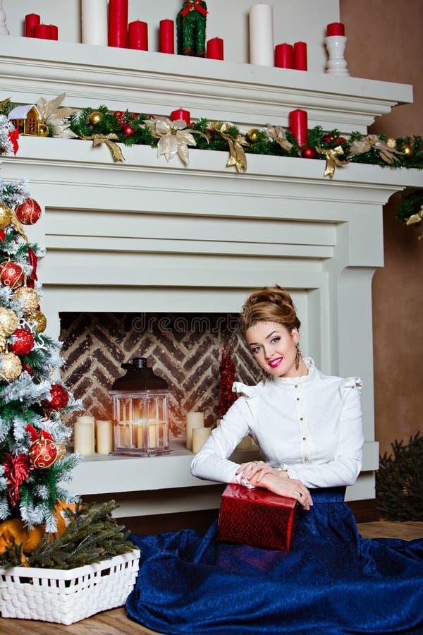 Όμορφο ξανθό κορίτσι σε μια μπλε συνεδρίαση φουστών κοντά στα Χριστούγεννα στοκ εικόνα