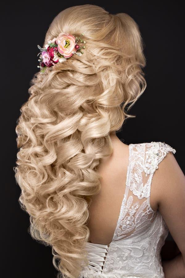 Όμορφο ξανθό κορίτσι στην εικόνα της νύφης με τα πορφυρά λουλούδια στο κεφάλι της Πρόσωπο ομορφιάς Πίσω άποψη Hairstyle στοκ εικόνα με δικαίωμα ελεύθερης χρήσης