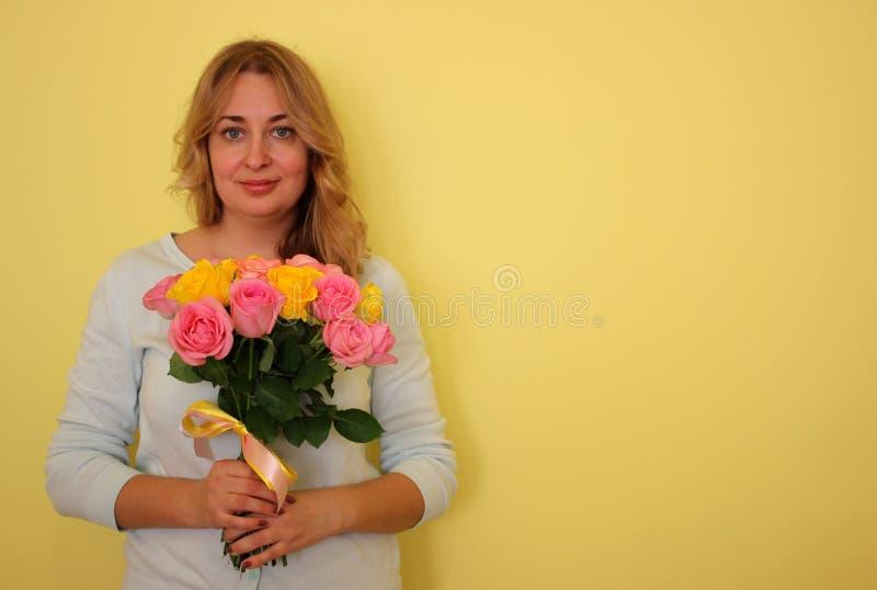 Όμορφο ξανθό κορίτσι στην μπλε ανθοδέσμη εκμετάλλευσης φορεμάτων των κίτρινων και ρόδινων τριαντάφυλλων σε ένα ανοικτό κίτρινο υπ στοκ εικόνα