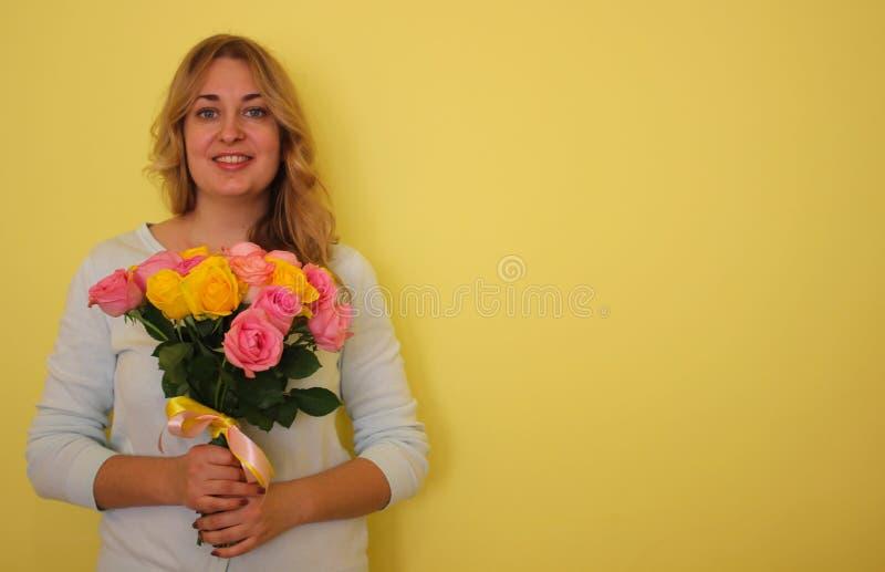 Όμορφο ξανθό κορίτσι στην μπλε ανθοδέσμη εκμετάλλευσης φορεμάτων των κίτρινων και ρόδινων τριαντάφυλλων σε ένα ανοικτό κίτρινο υπ στοκ εικόνες