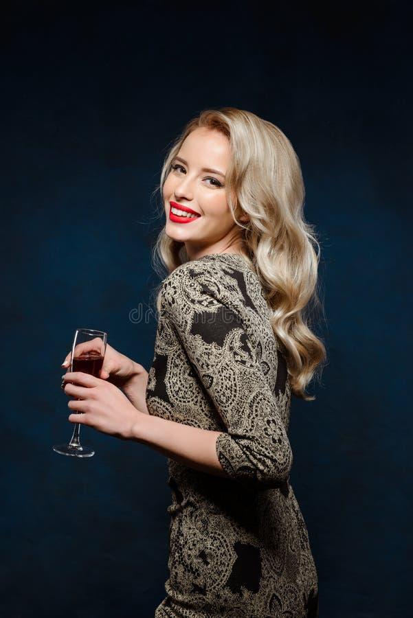 Όμορφο ξανθό κορίτσι στο χαμόγελο φορεμάτων βραδιού, που κρατά το γυαλί κρασιού στοκ φωτογραφία