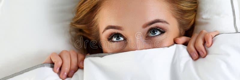 Όμορφο ξανθό κρύβοντας πρόσωπο γυναικών κάτω από την κάλυψη που βρίσκεται στο κρεβάτι στοκ φωτογραφίες