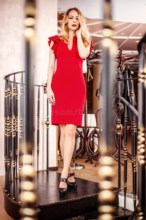 Όμορφο ξανθό κόκκινο καλά εφαρμόζον φόρεμα γυναικών στοκ φωτογραφίες με δικαίωμα ελεύθερης χρήσης