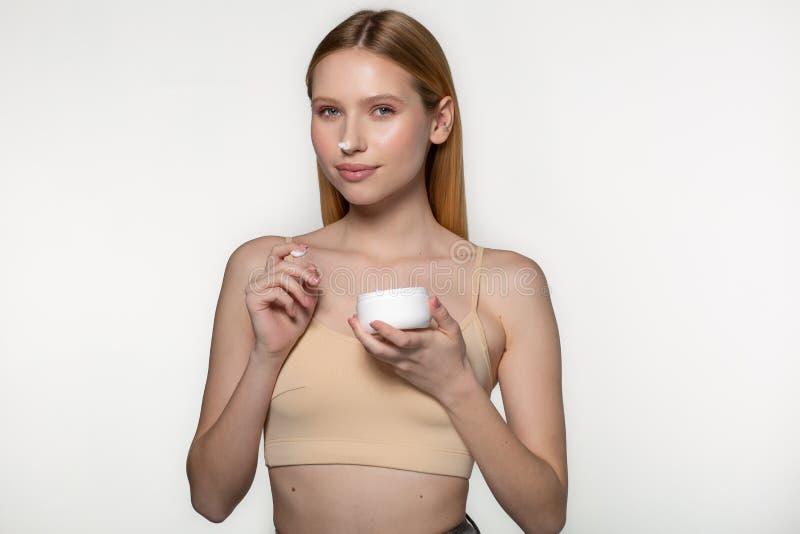 Όμορφο ξανθό τρυφερό βάζο γυναικών της κρέμας moisturizer Φρέσκο νέο πρόσωπο γυναικών κινηματογραφήσεων σε πρώτο πλάνο r στοκ εικόνες με δικαίωμα ελεύθερης χρήσης
