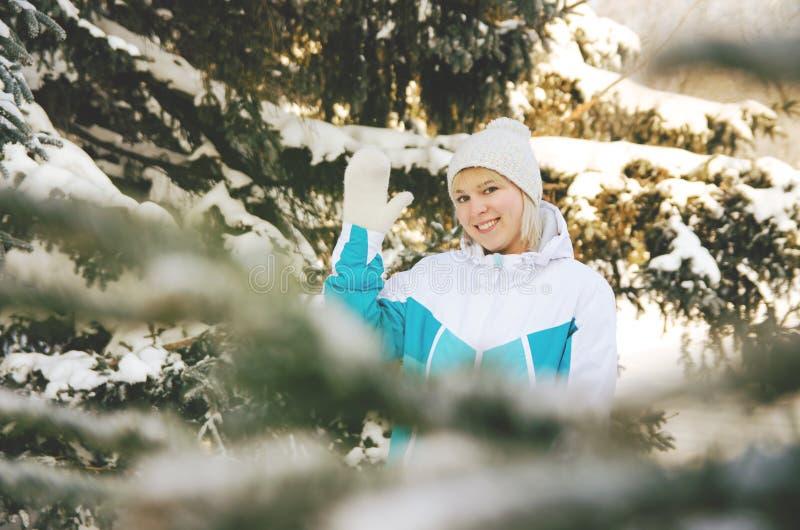 Όμορφο ξανθό χαμογελώντας κορίτσι που στέκεται μεταξύ των δέντρων έλατου στοκ εικόνες