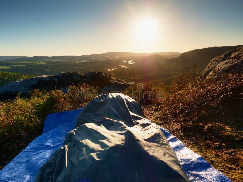 Όμορφο ξύπνημα σε έναν υπνόσακο στην προεξοχή βράχου Τα πουλιά τραγουδούν και ήλιος στον ορίζοντα στοκ φωτογραφία με δικαίωμα ελεύθερης χρήσης