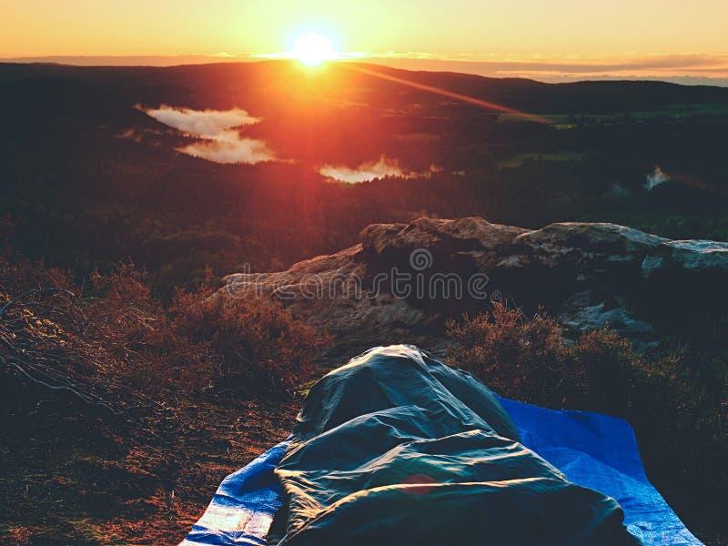 Όμορφο ξύπνημα σε έναν υπνόσακο στην προεξοχή βράχου Τα πουλιά τραγουδούν και ήλιος στον ορίζοντα στοκ εικόνες