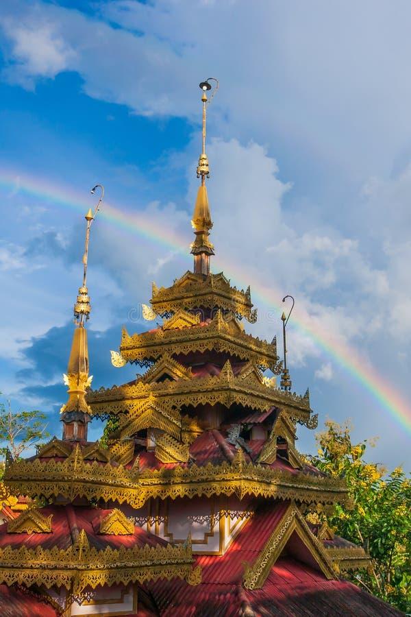 Όμορφο ουράνιο τόξο πέρα από τον αρχαίο ξύλινο ναό Shan-ταϊλανδικός ναός βουδισμού Τα τροπικά δέντρα είναι στα υπόβαθρα άνθισης Τ στοκ φωτογραφία