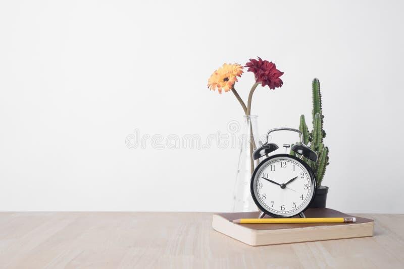 Όμορφο λουλούδι στο βάζο και ξυπνητήρι, βιβλίο, μολύβι στο ξύλο στοκ φωτογραφίες