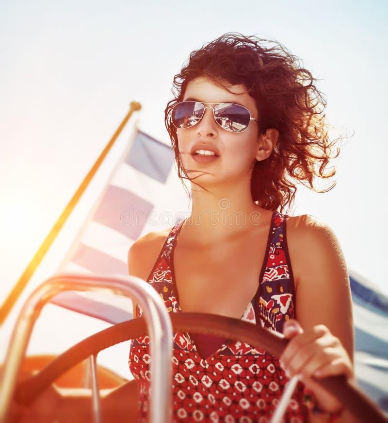 Όμορφο οδηγώντας sailboat γυναικών στοκ φωτογραφία