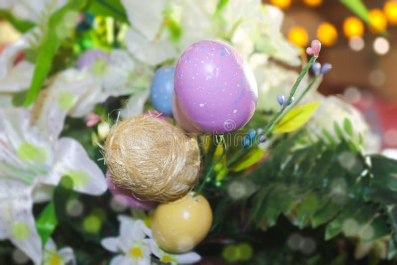 Όμορφο Πάσχα ανθίζει με τα χρωματισμένα και αυγά αχύρου με το υπόβαθρο bokeh - πορφυρό και ρόδινο και κίτρινο και πράσινο στοκ φωτογραφίες